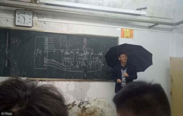 Thầy giáo vừa che ô vừa giảng bài trong lớp dột