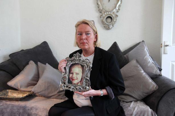 Mẹ nạn nhân bên di ảnh của con gái mình.
