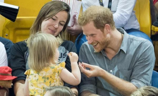 Hoàng tử Harry thân mật trêu đùa bé gái ăn trộm bỏng ngô của anh trong sự kiện thể thao dành cho người khuyết tật ở Canada hồi tháng 9 năm ngoái. Ảnh: Samir Hussen.