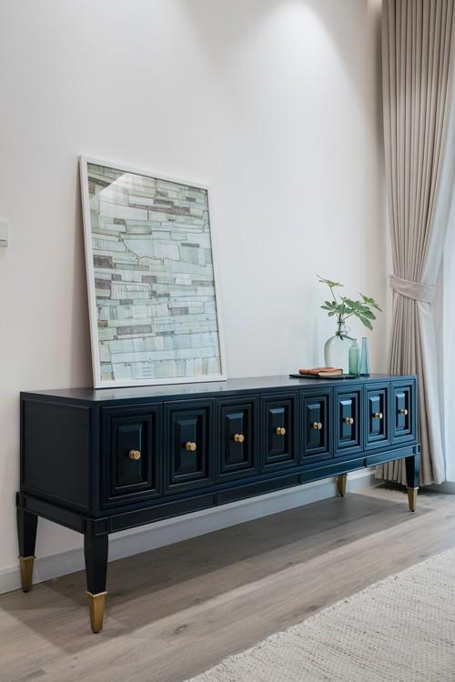 Ở phòng khách và phòng ngủ chính có thêm tủ đồ màu xanh đen với phần chân và tay nắm màu đồng. Các bức tranh, đồ trang trí ít nhưng được lựa chọn kỹ càng.