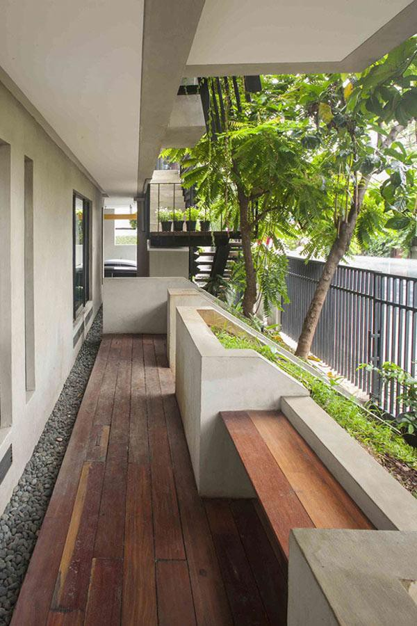 Mặt tiền của căn nhà cũng được xây lui vào, ngoài dành chỗ để xe còn được thiết kế thành một khu vực thư giãn với sàn gỗ, ghế và cây xanh đầy bóng mát.
