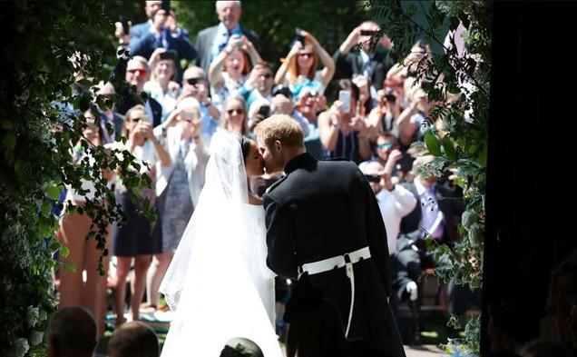 Hoàng từ Harry nắm tay công nương Meghan tiến ra cổng nhà nguyện. Hai người dừng lại, nhìn và trao nhau nụ hôn.