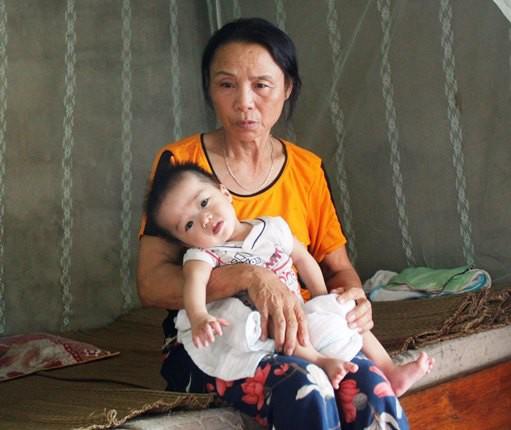 Bà Hà chăm sóc người cháu nội bị bệnh bại não.