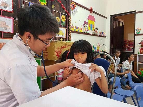 Em Hà Thị Lan, sinh năm 2010 đang được các bác sĩ Bệnh viện Tim Hà Nội thăm khám. Ảnh: Bảo Loan