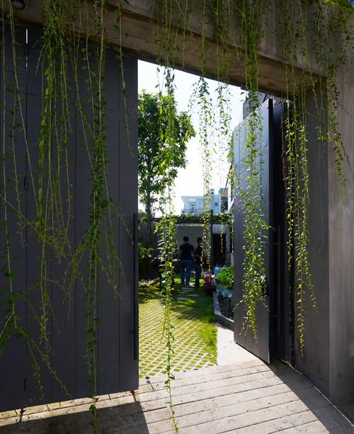 Lối cổng vào kín đáo, có gắn thiết bị chống trộm và camera an ninh, được làm mềm mại nhờ rèm cây buông rủ.