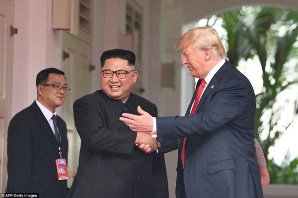 Cái bắt tay thân mật của ông Kim và ông Trump. Ảnh Straits Time