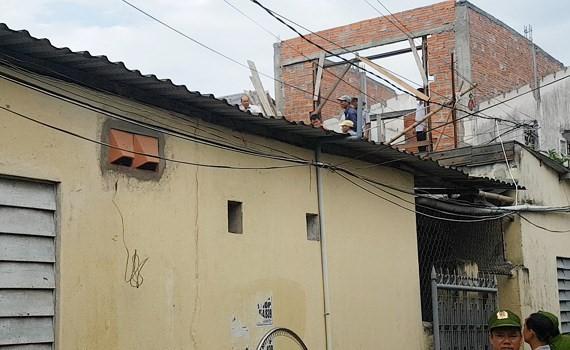 Thanh niên ngáo đá cố thủ trên mái nhà. Ảnh: Đ.Q.