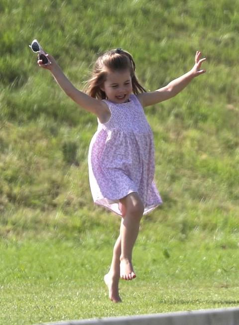 Charlotte vui vẻ chạy trên bãi cỏ khi cùng mẹ và anh trai tới cổ vũ bố William trong trận đấu polo hôm 10/6. Ảnh: PA.