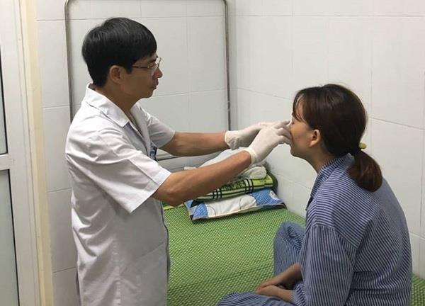 TS.BS Phạm Cao Kiêm đang điều trị cho bệnh nhân Đoàn Thị M. Ảnh:B.LOAN