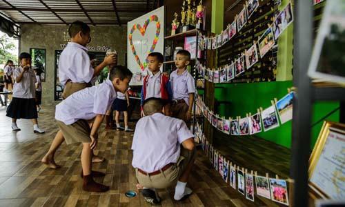 Bạn học của Adul ở trường Bang Wiang Phan thăm khu vực cầu nguyện cho đội bóng Lợn Hoang hôm 9/7. Ảnh: AFP.