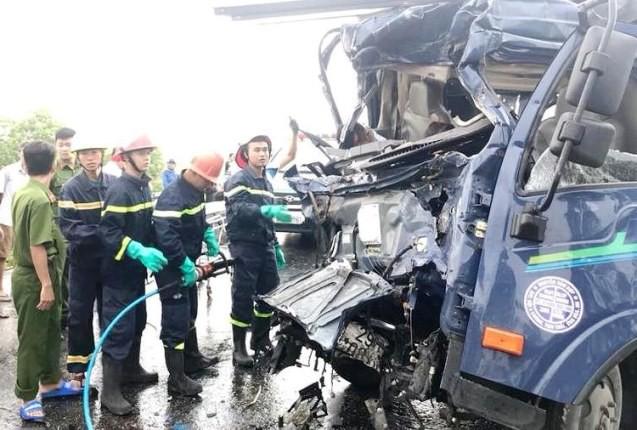 Lực lượng PCCC dùng dụng cụ cắt sắt để đưa thi thể tài xế xe tải ra ngoài.