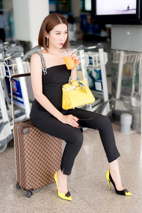 Người đẹp nghỉ ngơi, uống nước cam giải khát trong khi chờ tới giờ làm thủ tục lên máy bay.