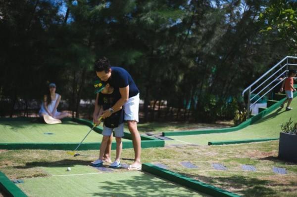 Kim Lý hướng dẫn bé Subeo, con trai Hà Hồ đánh golf.