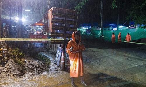 Một cảnh sát Thái Lan đứng gần khu vực giải cứu đội bóng nhí mắc kẹt trong hang Tham Luang khi trời mưa lớn đêm qua. Ảnh: AFP.