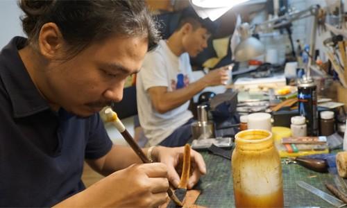 Anh Cao Duy Long (trái) và cộng sự duy nhất cặm cụi làm dây đồng hồ da trong căn xưởng nhỏ xíu của mình ở phố Liên Trì (Hoàn Kiếm, Hà Nội). Ảnh: Trọng Nghĩa.