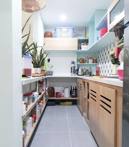 Người vợ rất thích nấu nướng nên đồ dùng bếp nhiều. Gia chủ đã tận dụng tối đa các kệ thấp chạy dọc quanh bếp để chứa đồ. Đồng thời mở thông không gian bếp và phòng khách để tạo sự rộng rãi thoáng đãng cho căn nhà, cũng là để tạo sự tiếp xúc tuyệt đối giữa các thành viên trong gia đình.