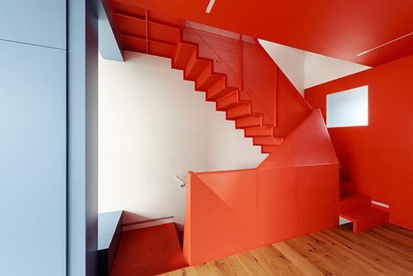 Góc cầu thang hai tầng nổi bật với sắc đỏ rực rỡ