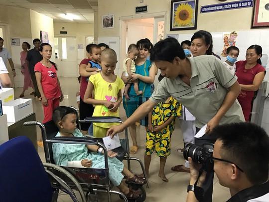 Đại diện gia đình cháu H và T trao tiền hỗ trợ lại cho các bệnh nhân có hoàn cảnh khó khăn tại Bệnh viện Phụ sản Nhi Đà Nẵng. Ảnh: NLD