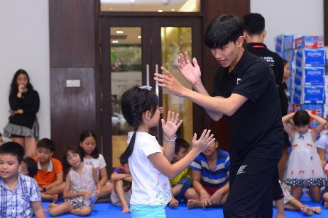 Huấn luyện viên đang dạy cô học viên nhỏ cách thoát thân trong tình huống giả định bị kẻ xấu túm tóc khống chế
