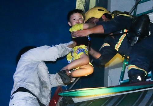 Lính cứu hỏa đưa cư dân Carina thoát khỏi vụ cháy rạng sáng 23/3. Ảnh: Quỳnh Trần.