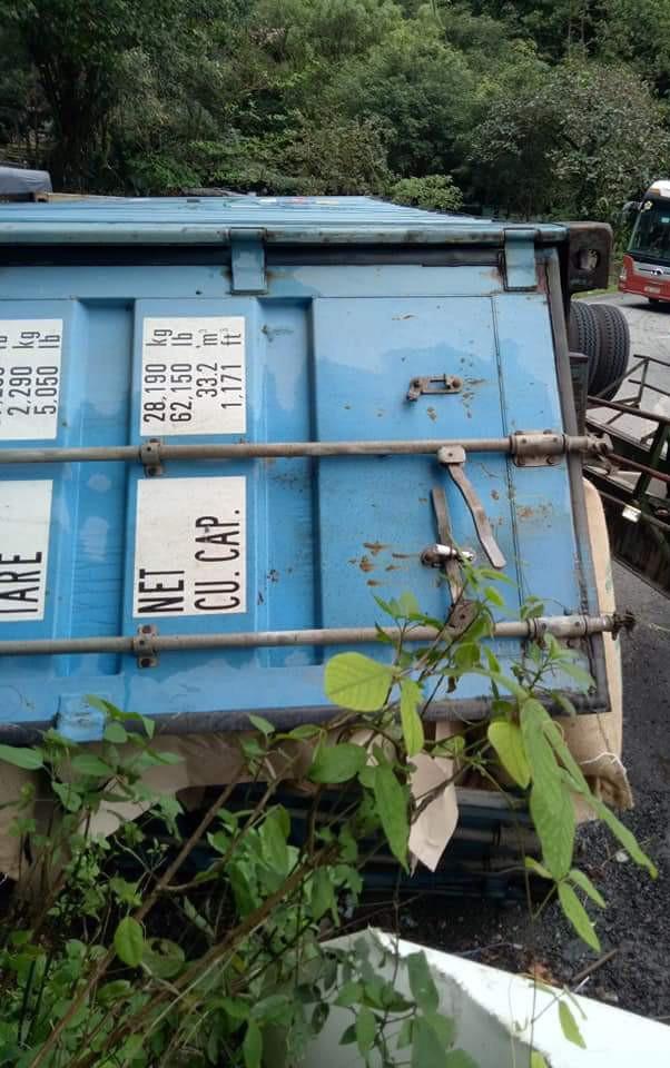 Chiếc container lật nghiêng, phơi bụng, người dân phá cửa cứu tài xế mắc kẹt trong cabin