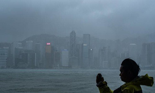 Người đàn ông đứng chụp ảnh tại Hong Kong khi bão Mangkhut đổ bộ vào hôm qua. Ảnh: AFP.