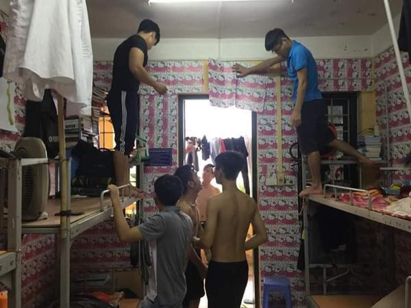 Gần 10 nam sinh lực lưỡng thay nhau dán tường.