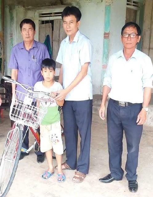 Bé Danh được Đại đức Thích Tâm Phương - Trụ trì chùa Nhiễu Long gửi tặng chiếc xe đạp nhân năm học mới. Ảnh Nguyễn Phú Hàm.