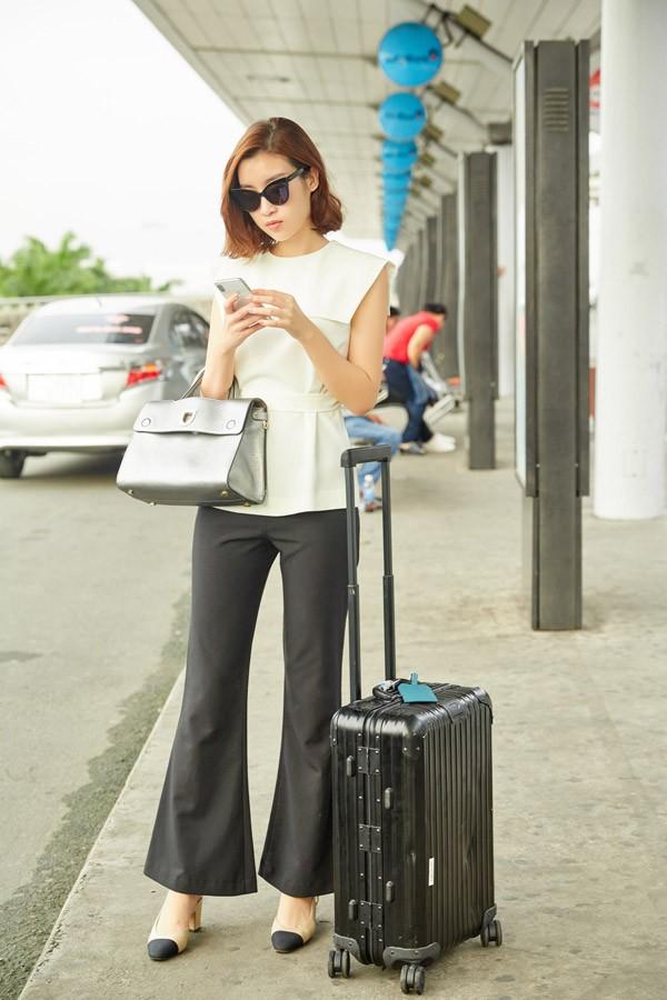 Hoa hậu Việt Nam 2016 mix áo trắng thắt eo cùng quần ống loe. Cô mang giày hiệu, xách túi ánh bạc đắt đỏ cùng mắt kính thời thượng.