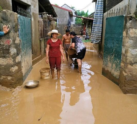 Nước bắt đầu rút, người dân xã Cẩm Phong vật lộn trong bùn nước để thau rửa nhà cửa