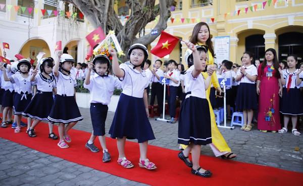 Sáng nay Đà Nẵng nắng nhẹ. Hơn 500 học sinh lớp 1 ở Trường Tiểu học Phù Đổng đội mũ bảo hiểm, cầm lá cờ Tổ quốc, được các anh chị khối lớp 4, 5 chào đón vào trường bằng nhưng chàng pháo tay. Nhiều em nhỏ đi chưa theo hàng lối, mặt còn ngái ngủ. Ảnh: Nguyễn Đông (VnExpress)