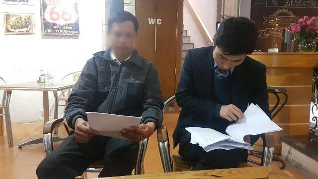Luật sư Phan Văn Hào (phải) đang nghiên cứu hồ sơ vụ việc.