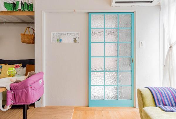 Chiếc cửa xanh xinh xắn hài hòa với các vật dụng xung quanh dẫn vào ngôi nhà của vợ chồng trẻ.