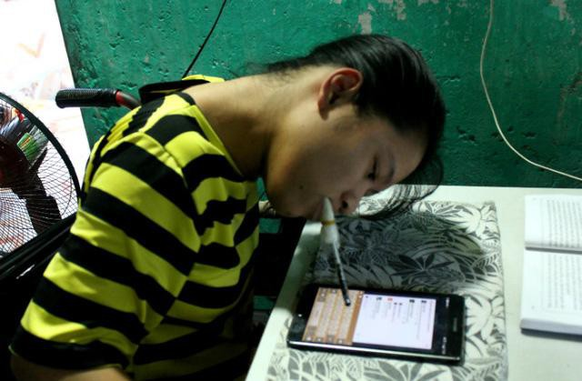 Hương ngậm bút gõ chữ trên máy tính bảng để tương tác với mọi người trên mạng xã hội. Ảnh Kim Bảo Ngân