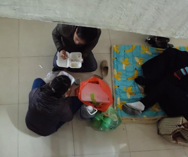 Một gia đình trẻ ăn vội bữa trưa dưới chân cầu thang. (Ảnh: Lê Bảo).