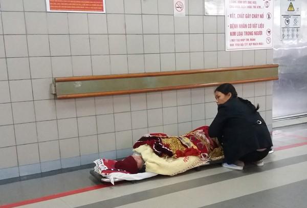 Một bệnh nhân được nằm tạm phía ngoài đợi đến lượt điều trị. (Ảnh: Minh Ngọc).