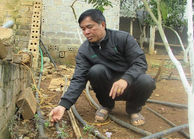 Ông Dũng đang bật hệ thống nước để tưới tiêu cho vườn cây ở trang trại