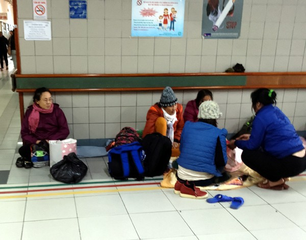 Người dân phải trải chiếu, chăn và ăn cơm trưa dưới hành lang bệnh viện. (Ảnh: Lê Bảo).