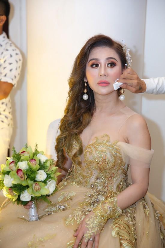 Cô được chuyên gia make-up lau mồ hôi trong lúc ngồi đón khách.