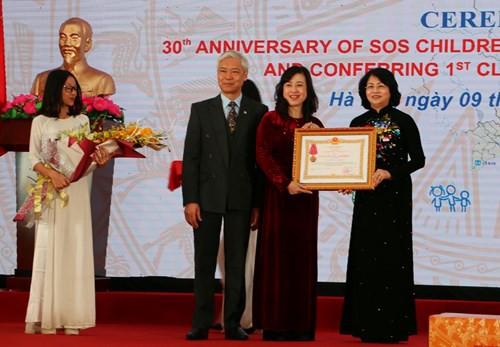 Phó Chủ tịch nước Đặng Thị Ngọc Thịnh (bìa phải) trao Huân chương Lao động hạng Nhất cho Làng Trẻ em SOS Việt Nam.