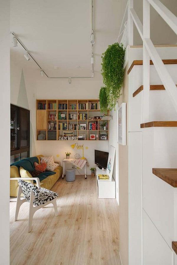 Phòng khách tuy nhỏ nhưng chẳng thiếu thứ gì, ấn tượng nhất phải kể đến giá sách gỗ khá lớn treo trên tường nhà.