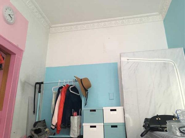 Chiếc tủ quần áo trắng đặt gọn trong góc phòng.