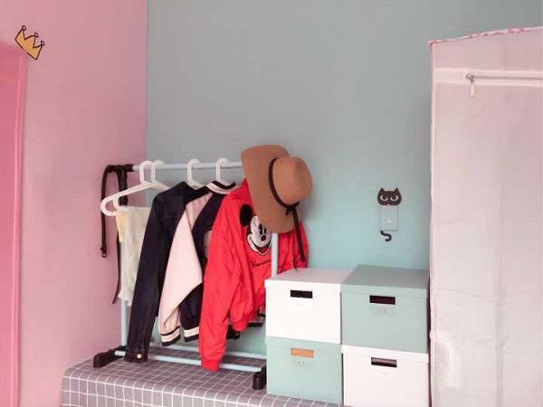 Bên cạnh đó là chiếc bàn cũ được tận dụng đặt hộp đựng đồ và móc nhỏ treo quần áo.