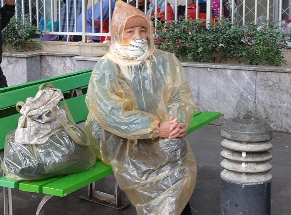 Một người phụ nữ co ro dưới trời mưa phùn, gió lạnh. (Ảnh: Lê Bảo).