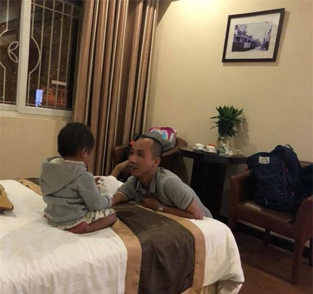 Anh Tín - chồng chị Phương thường xuyên nói chuyện với Pàng để em cảm thấy bớt đau đớn do xương chân bị co rút hàng đêm. Ảnh NVCC