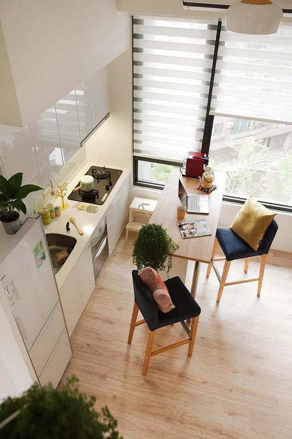 Diện tích khiêm tốn nhưng trong bếp vẫn đủ chỗ đặt một bộ bàn ăn quầy bar khá hiện đại bên cạnh cửa sổ đầy nắng. Khi cần thiết, chiếc bàn này có thể sử dụng như bàn làm việc.