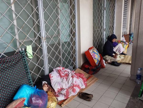 Tại hành lang của tòa nhà tầng 1, hàng chục người ôm chăn chiếu nằm ngủ dù trời lạnh buốt. (Ảnh: Lê Bảo).