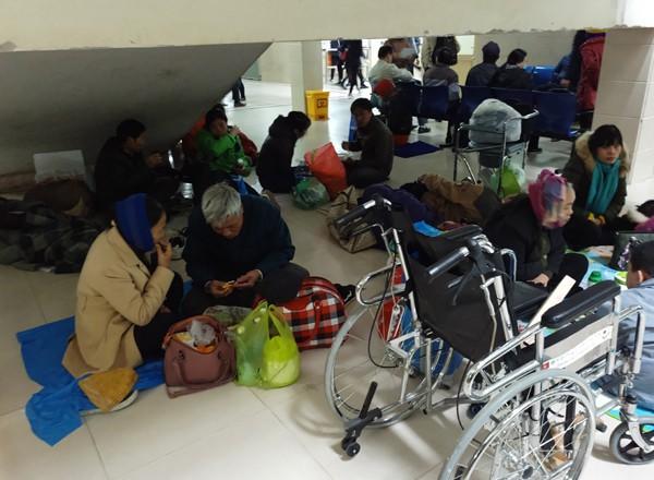 Trong khi đó tại khu vực khác dưới chân cầu thang, hàng chục người nhà bệnh nhân, bệnh nhân ngồi nghỉ trưa, ăn cơm. (Ảnh: Lê Bảo).