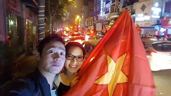 Hình ảnh đời thường của vợ chồng MC Anh Tuấn khi ra đường ăn mừng chiến thẳng của đội tuyển Việt Nam.