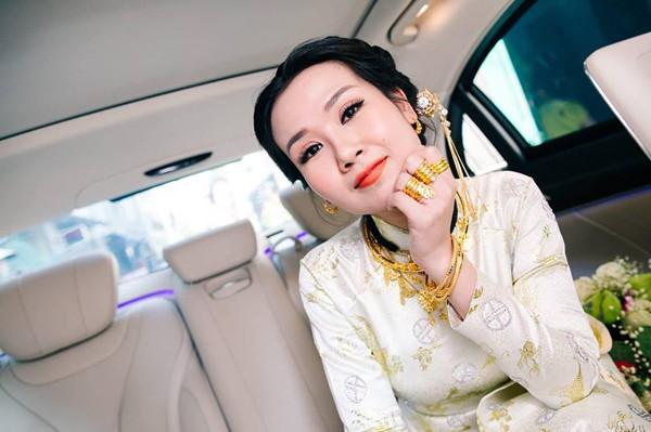 Võ Hạ Trâm khoe vàng trĩu cổ đầy tay khi ngồi trên xe hoa.